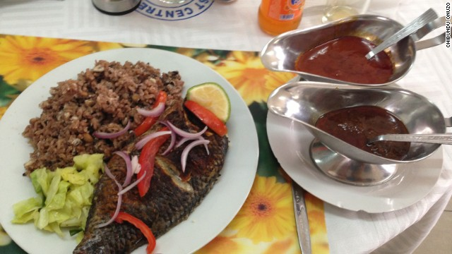 A culinary marvel found in Accra, grilled tilapia with waakye and tomato sauce.