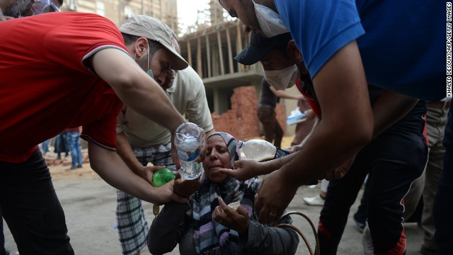 Egyptians help a woman suffering from tear gas exposure in a street leading to Rabaa al-Adawiya mosque in Cairo on August 14.