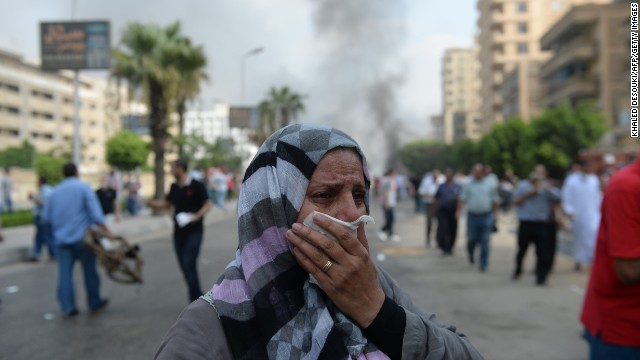 A woman tries to protect herself from tear gas in Cairo on August 14.
