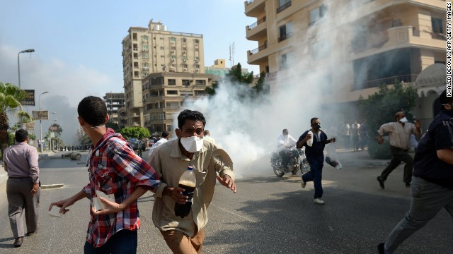 Muslim Brotherhood supporters run from tear gas in a street leading to Rabaa al-Adawiya mosque in Cairo on August 14.