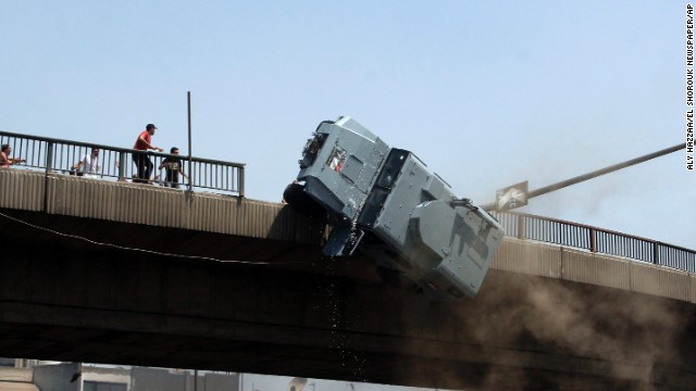 Supporters of Morsy push a police vehicle off the 6th of October Bridge in Cairo on August 14.