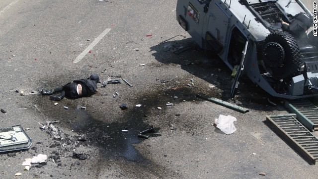 A member of the Egyptian security forces lies on the ground in Cairo on August 14 after a police vehicle was pushed off the 6th of October Bridge.