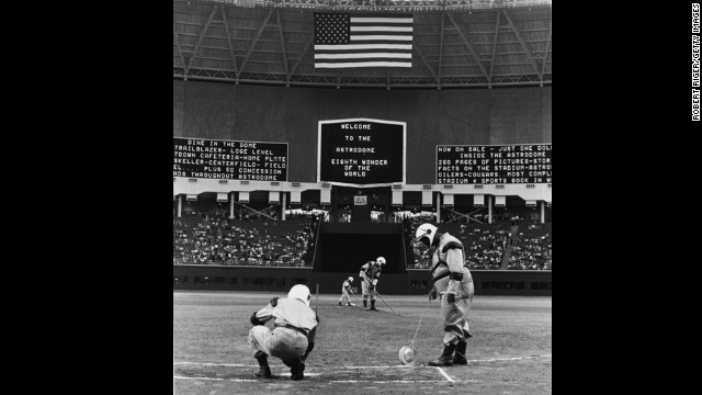 Groundskeepers wear spacesuit uniforms as they prepare for the first game in the Astrodome on April 12, 1965.