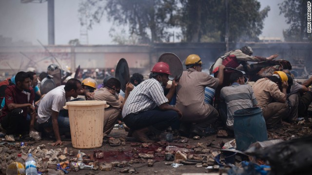 Supporters of ousted Egyptian President Mohammed Morsy take cover from during clashes in Cairo's Nasr City district.