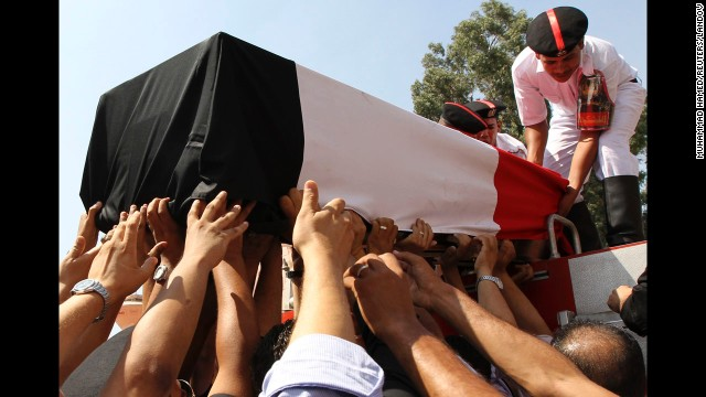 People reach for a coffin on Thursday, August 15, during a funeral for police officers killed during a crackdown at two protest camps in support of Morsy.