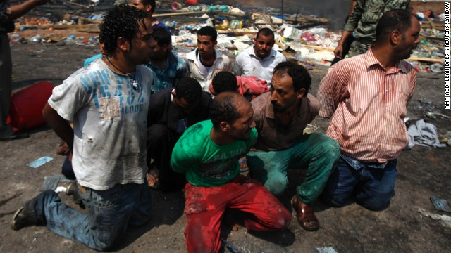 Men are detained near a burned section of Rabaa Al-Adawiya mosque in Cairo on August 15.