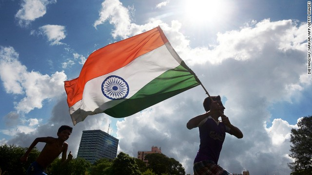 Indian youths run in a field with their national flag.