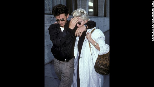 Then-husband Sean Penn shields Madonna from the paparazzi during a lunch break in New York City on August 13, 1986.