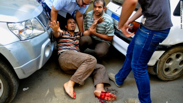 A protester wounded during clashes braces for help outside of a church on Mourad Street in Giza on August 16.