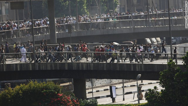 Morsy supporters march in Cairo. Gunfire was heard from the overpass as tear gas was fired.