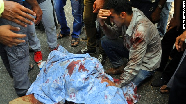 A group of men gather around an injured protester in Giza on August 16.