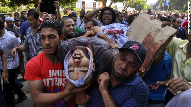 Demonstrators and Muslim Brotherhood supporters carry the body of a man apparently shot during clashes with security forces in Giza district on the outskirts of Cairo on August 16.