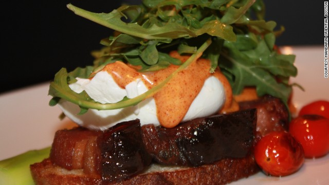 On the menu at the Mandarin Oriental Boston: A twist on the classic bacon and eggs combo includes two poached eggs, grilled and glazed thick cut bacon on grilled sourdough bread with roasted tomato arugula and smoked pimenton hollandaise.
