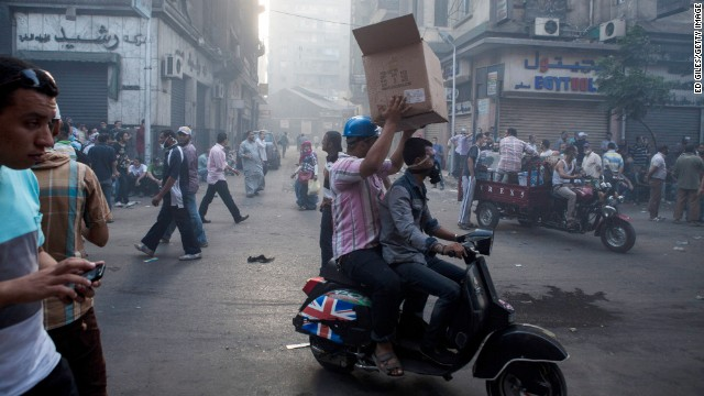 Morsy supporters carry supplies while violent clashes continue to take place near Ramses Square on August 16.