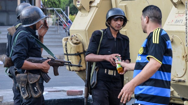 An Egyptian man offers a bottle of juice to policemen as clashes between Morsy supporters and security forces continue in Cairo on August 16.
