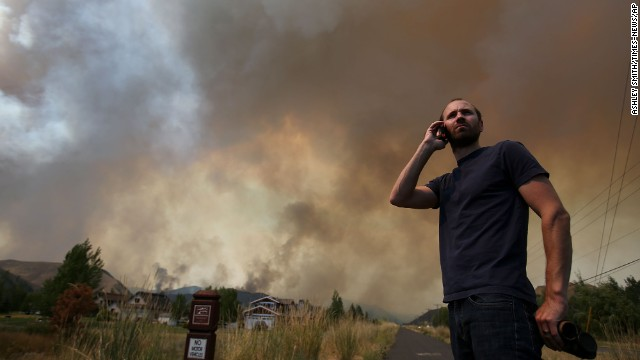 Kevin Bullock, of Bellevue, Idaho, talks on a cell phone as smoke from the wildfire envelops a neighborhood.