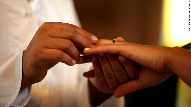 Natasha Vitali, left, and Melissa Ray exchange rings during their wedding at the Auckland Unitarian Church in Auckland on August 19.