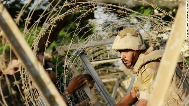 A soldier sets up barbed wire in anticipation of protesters outside the constitutional court in Cairo on Sunday, August 18, 2013. During the previous week about 900 people -- security forces as well as citizens -- had been killed. Deaths occurred when the military used force to clear supporters of ousted president Mohamed Morsy from two sit-in sites in Cairo, and violence raged after Morsy s