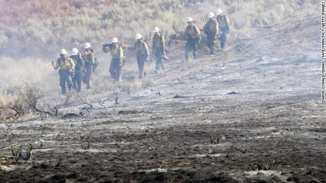 A firefighting team walks along a fire line near homes on Croy Road and the Rotorun ski hill west of Hailey, Idaho, on Saturday, August 17. A wildfire raging across the central mountains of Idaho forced the evacuation of 200 homes in the tourist town of Hailey as firefighters lost ground against a blaze threatening the nearby international ski destination of Sun Valley.
