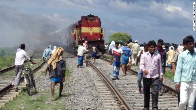 Train coaches of the Rajya Rani Express burn after crashing into a crowd of pilgrims in Khagaria district on August 19, 2013.