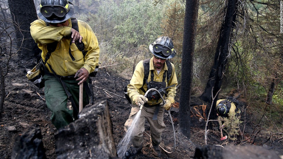 Firefighters with private contract company Great Basin Fire douse part of the 104,457-acre Beaver Creek Fire in the Baker Creek area of Ketchum, Idaho, on Monday, August 19. The fire has forced the evacuation of several neighborhoods.