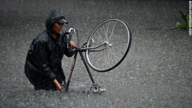 A man guides his bike through flood waters that submerged parts of the financial district of Makati on August 20.