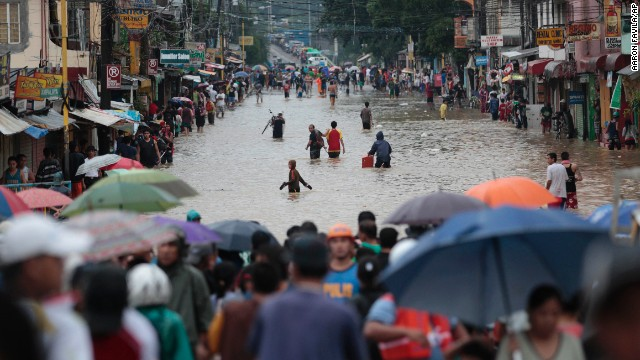 People cross a flooded street to evacuate to higher ground in Marikina City, Philippines, on Tuesday, August 20. Tens of thousands of Filipinos have been forced from their homes and at least seven have died due to heavy rains and flooding.