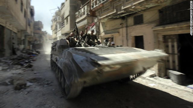 Syrian Army soldiers patrol a devastated street in Homs on Wednesday, July 31.