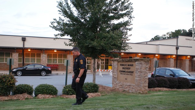 "A policeman walks in front of Ronald E. McNair Discovery Learning Academy after a shooting incident in Decatur, Georgia, on Tuesday, August 20. Michael Brandon Hill, 20, opened fire at the school armed with an AK-47 ""and a number of other weapons,"" police said. There were no reports of injuries."