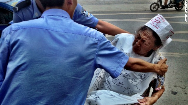Police detain an elderly demonstrator on August 21 who was protesting against the Chinese justice system outside the court in Jinan.