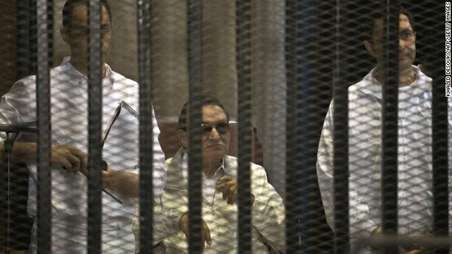 Mubarak and his sons Gamal, left, and Alaa are seen behind the defendants' cage during their retrial at the Police Academy in Cairo on June 8. Mubarak was granted a retrial in January. On August 21, a court ordered Mubarak be freed, pending his retrial.
