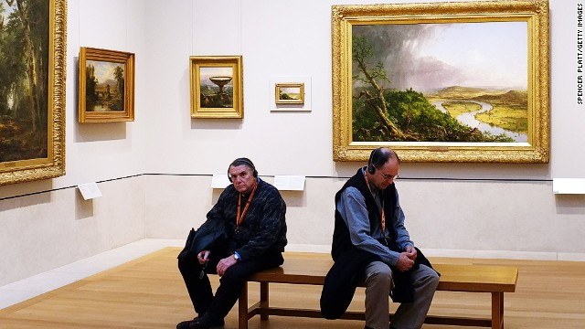Two men sitting in an art museum