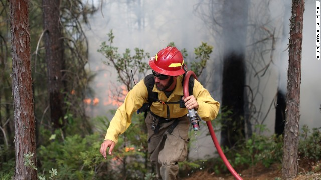 A firefighter from the Colorado-based South Arkansas Fire District carries a hose as he monitors the Rim Fire on August 22, in Groveland, California.