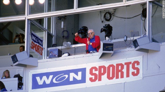 Chicago Cubs baseball announcer Harry Caray conducts fans singing