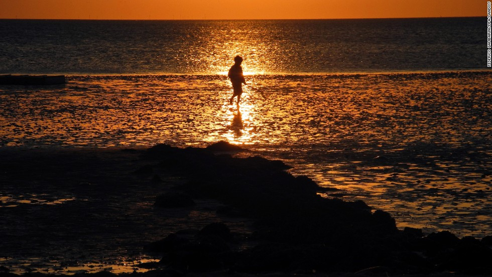 A boy walks along the shore in Utersum on the North Sea island of Foehr, Germany, on Saturday, August 24. Click through to see other images of weather around the world.