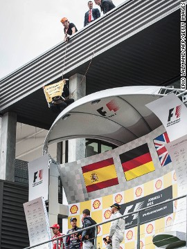 A member of Greenpeace also managed to unfurl a banner above the winner's podium at the end of the race, where drivers Sebastian Vettel, Fernando Alonso and Lewis Hamilton addressed the crowd.