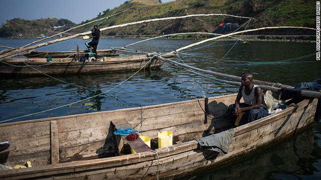 "A fisherman sits in a boat on the shore of Lake Kivu in Goma in August. ""There are no big fish because of the gas; we only catch small whitebait,"" one said of the carbon dioxide and methane that saturate the lake."