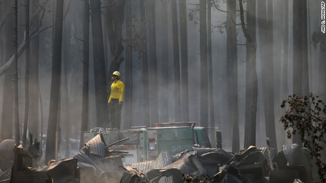A firefighter stands on top of a fire truck at a campground destroyed by the Rim Fire near Yosemite National Park on August 26. The massive wildfire grew on Monday to become the 13th largest in state history, state fire authorities said.