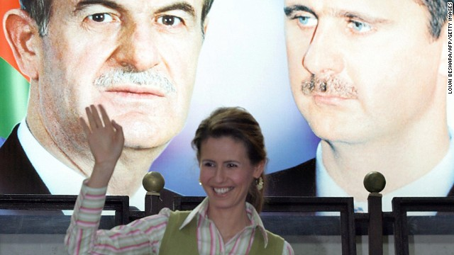 The Syrian first lady waves under a portrait of her husband, right, and his late father, former President Hafez al-Assad, during the opening ceremony of the Syrian Special Olympics in Damascus, Syria, on May 15, 2006.