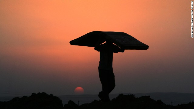 A Syrian-Kurdish man carries a mattress at sunset at the Quru Gusik refugee camp, east of Arbil, the capital of the autonomous Kurdish region of northern Iraq, on Tuesday, August 27. More than 50,000 Syrian refugees have crossed into Iraq's Kurdish region in less than two weeks as authorities rush to house them in more permanent camps.