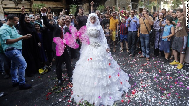 A crowd cheers as a Lebanese bride and groom pose for pictures at the site of a car bomb explosion just days before in Beirut's Rweiss neighborhood .