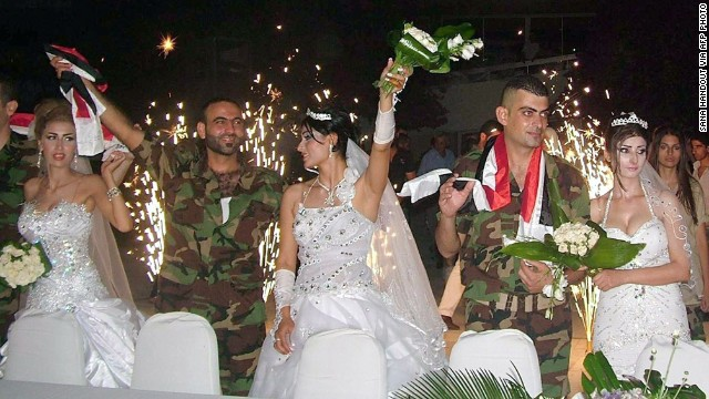 Syrian soldiers celebrate with their their brides during a group wedding in the Latakia province, western Syria.