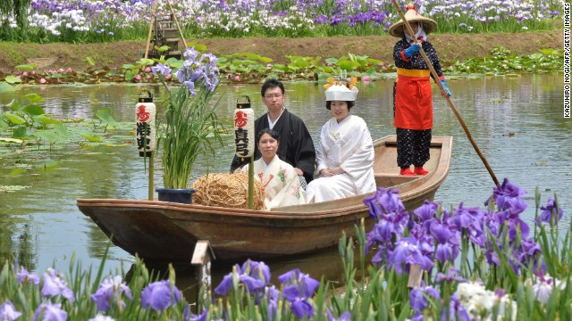 A Japanese bride and her groom sail through a canal for their wedding procession at the irises garden after their wedding ceremony at Katori city in Chiba prefecture.