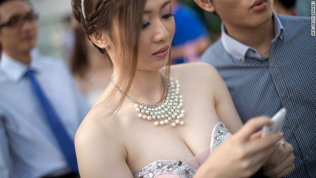 A bride checks her messages while getting ready for a group picture after a mass wedding outside a Chinese temple in Kuala Lumpur on December 12, 2012.
