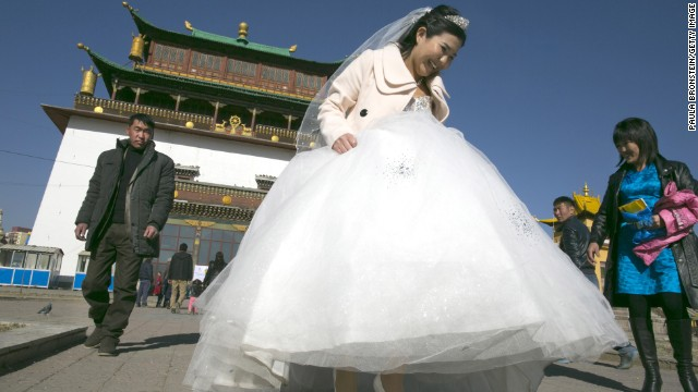 A bride walks holding her wedding dress at the Gandan monastery on a special day on the Lunar calendar for wedding ceremonies October 18, 2012 Ulaanbataar, Mongolia.
