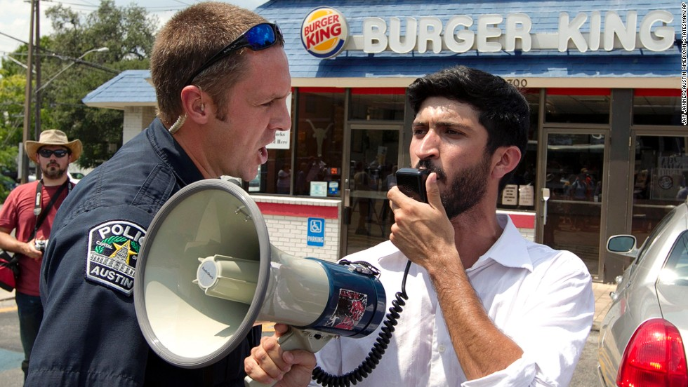 A police officer orders Greg Casar of the Workers Defense Project to get off the property of a Burger King in Austin, Texas, on Thursday, August 29. Casar was leading a group of about 200 people supporting the nationwide fast food strike. Fast food workers in 60 cities across the country walked off the job Thursday in a protest for higher wages.
