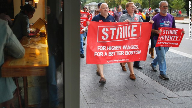 Demonstrators pass a cafe during a march through the streets of Boston on August 29.