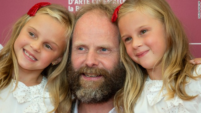 "Twins Pia Keelman, left, and Chiara Keelman pose at the festival with director Philip Groning for the film ""The Police Officer's Wife"" on August 30."