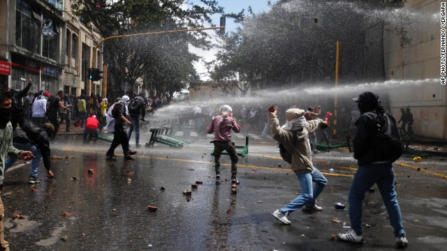 Students dodge police water canons as they protest in downtown Bogota, Colombia, on August 29, 2013.