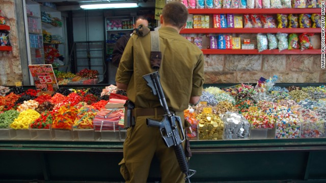 In among the holy sites, daily life roars on: souks crowd the narrow, stone-flagged alleyways, children go to school, libraries jostle with restaurants. In this file photo, a soldier buys candy at the Mahane Yehuda Market.